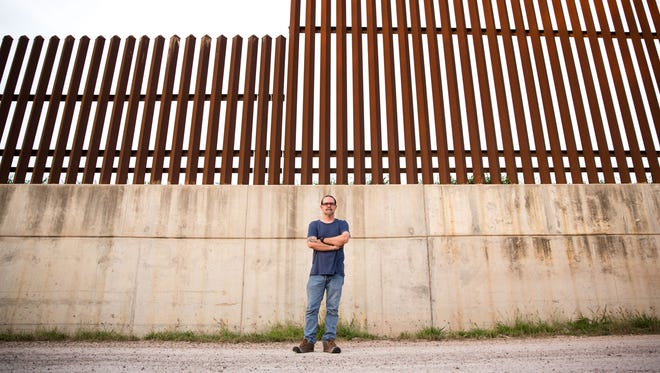 Scott Nicol, co-chair of the Sierra Club's borderlands team, stands in front of the border fence in Hidalgo in far South Texas. This section, which sits atop a levee, runs between a national wildlife refuge and a local nature center.