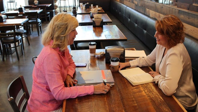 Laura Poisson (right), President of ClearRock Inc. in Boston, discusses with a client how her company's outplacement and career transition services contribute to meaningful career advancement. (Courtesy of ClearRock Inc.)