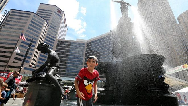 The Tyler Davidson Fountain was a good place for a misting during the Taste of Cincinnati. Getting more than a misting was Bradley Ferrell, 6, of Middletown.