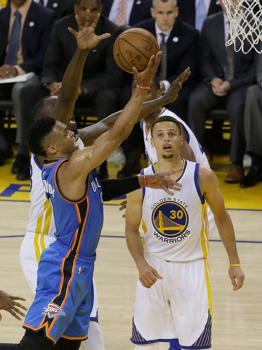 Oklahoma City Thunder guard Russell Westbrook, front left, shoots against Golden State Warriors forward Draymond Green, back left, and guard Stephen Curry (30) during the first half of Game 2 of the NBA basketball Western Conference finals in Oakland, Calif., Wednesday, May 18, 2016. (AP Photo/Jeff Chiu)