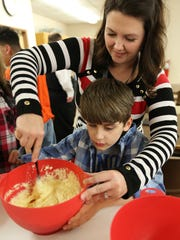 Trey Mauzy, with a little assistance from Jackie Williams, mashes up potatoes as he helps to prepare shepherd's pie at the Kentucky School for the Blind.March 167, 2017