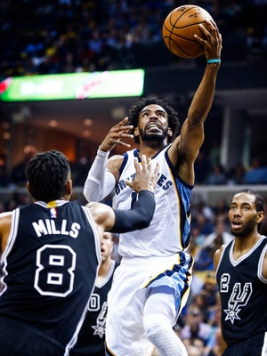 Memphis' Mike Conley (middle) drives for a layup against San Antonio's Patty Mills (left) and Kawhi Leonard (right) during second quarter action of their first round NBA playoff game at the FedExForum.