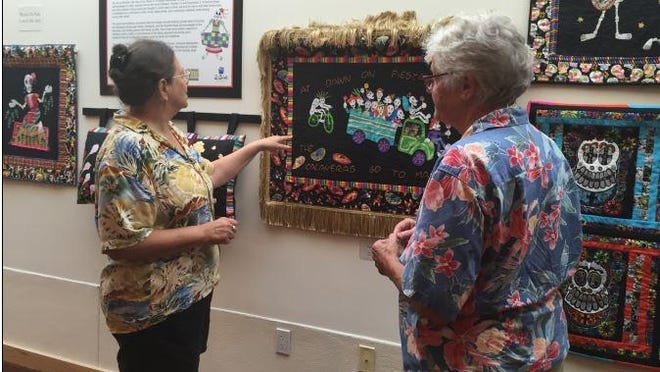 """Palm Springs residents Cathy Parker and Trudy Elm admire """"Fiesta Day"""" by Palm Springs artist Laura Fiedler at the La Quinta Civic Center's """"Follow the Thread"""" quilt exhibit."""