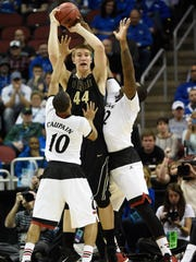 Mar 19, 2015; Louisville, KY, USA; Purdue Boilermakers center Isaac Haas (44) looks to pass as Cincinnati Bearcats guard Troy Caupain (10) and Cincinnati Bearcats center Coreontae DeBerry (22) defend during the second half in the second round of the 2015 NCAA Tournament at KFC Yum! Center. Mandatory Credit: Jamie Rhodes-USA TODAY Sports