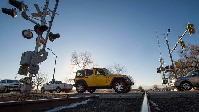 Traffic flows over railroad tracks at the intersection of Vine Drive and Lemay Avenue on Thursday in Fort Collins. A proposal would allow the building of an overpass or underpass to alleviate traffic delays related to train activity in the area.