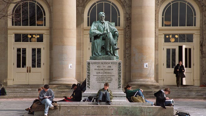 Cornell University students study beside a statue of Andrew Dixon White outside Goldwin Smith Hall.