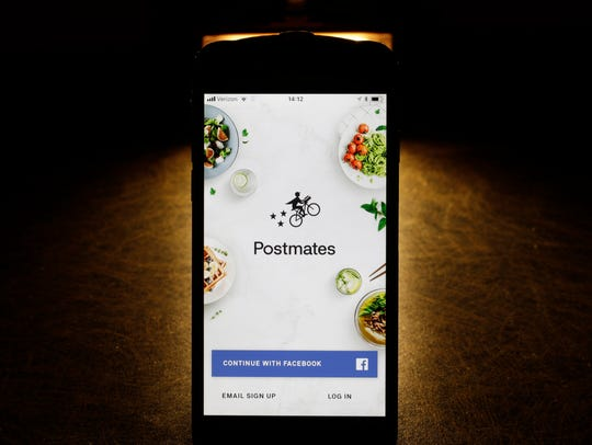 The Postmates app is shown on an iPhone. More restaurants have been offering delivery by teaming up with third-party delivery services like Postmates and Uber Eats.