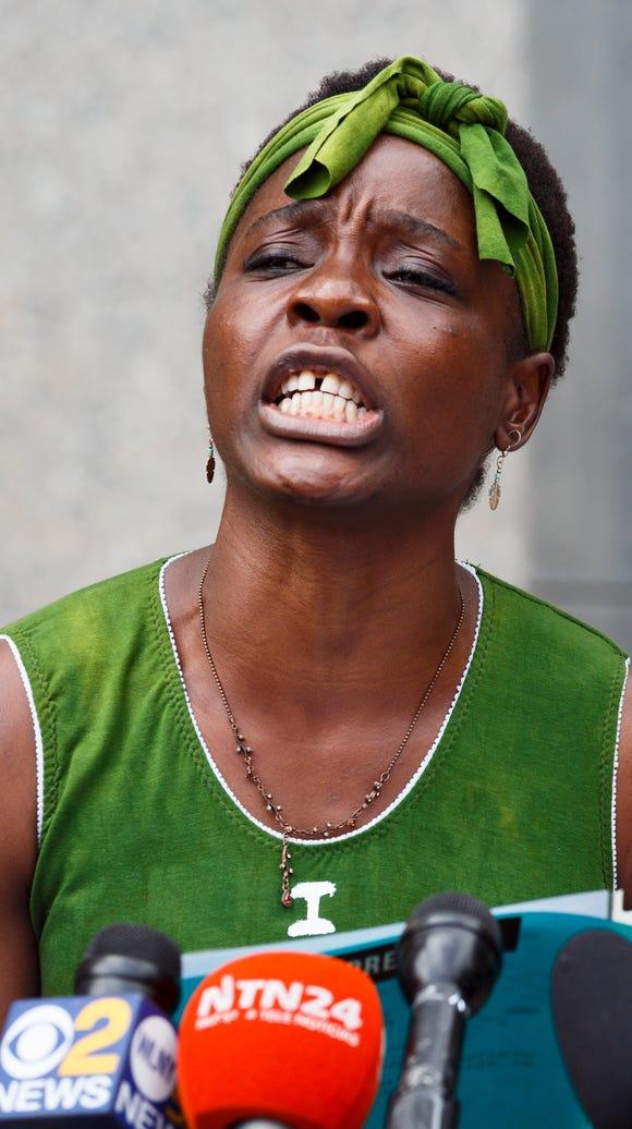Activist Patricia Okoumou talks to reporters outside