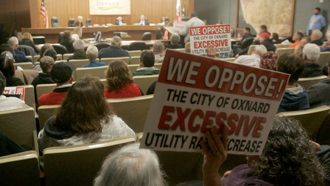 Signs noting oppostiion to an increase in fees for water and sewer services are raised by audience members during the Oxnard City Council meeting Jan. 19, 2016