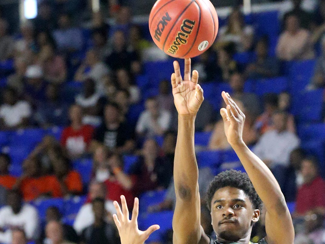 Hillsboro's Darius Ferguson (1) goes up for a shot as Memphis East's Nikcolauz Merriweaher guards hime during the State Tournament Quarterfinal game Wednesday at MTSU.