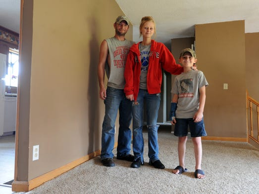 Mike Lane stands with his wife and their son in their temporary housing in South Zanesville.