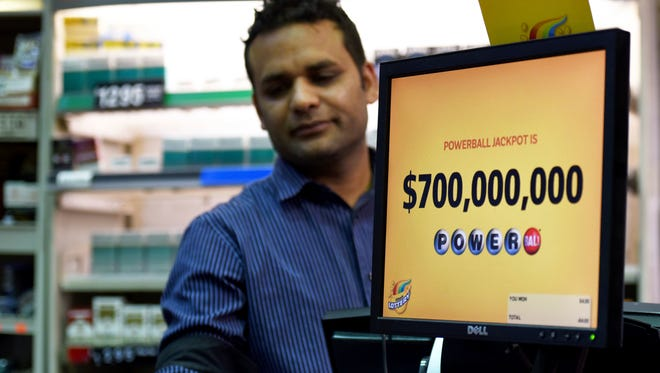 The jackpot of $700 million is shown on the screen as Malik Imran serves a customer in this Chicago store on Aug. 22, 2017. This Powerball lottery game makes it the second-largest in U.S. history.