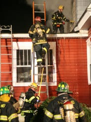 Firefighters climb a ladder to get on the roof to extinguish