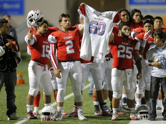 Teammates hold the jersey of Carlos Robles before a game at Rabobank Stadium. Robles, a sophomore defensive end on the North Salinas High football team, was shot and killed the previous week. The suspect is scheduled for court Jan. 29.