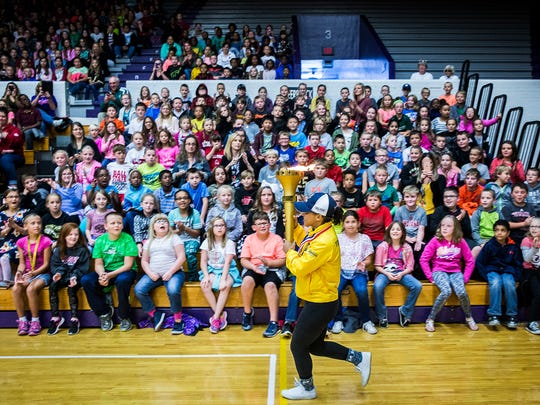 Delyn Harty-Isom runs through the Muncie Fieldhouse with the Bicentennial Torch Tuesday morning.