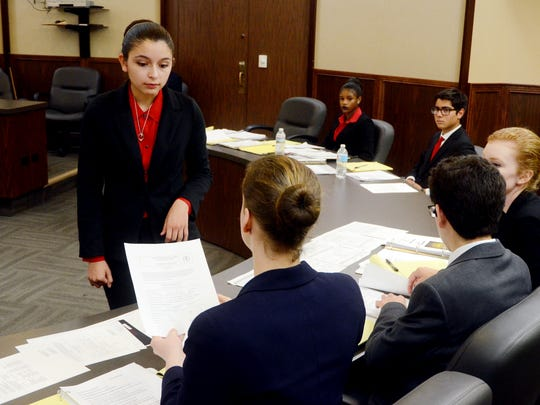 Incarnate Word Acadmey student Sophia Aguirre (left), competing as an attorney, shows evidence to Ray High School students competing as prosecuting lawyers  Saturday, Feb. 4, 2017, during the Region 2 high school mock trial competition at the Nueces County Courthouse.
