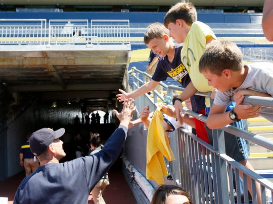 Michigan head coach Jim Harbaugh greets fans as he leaves the field Aug. 6, 2015, on media day.