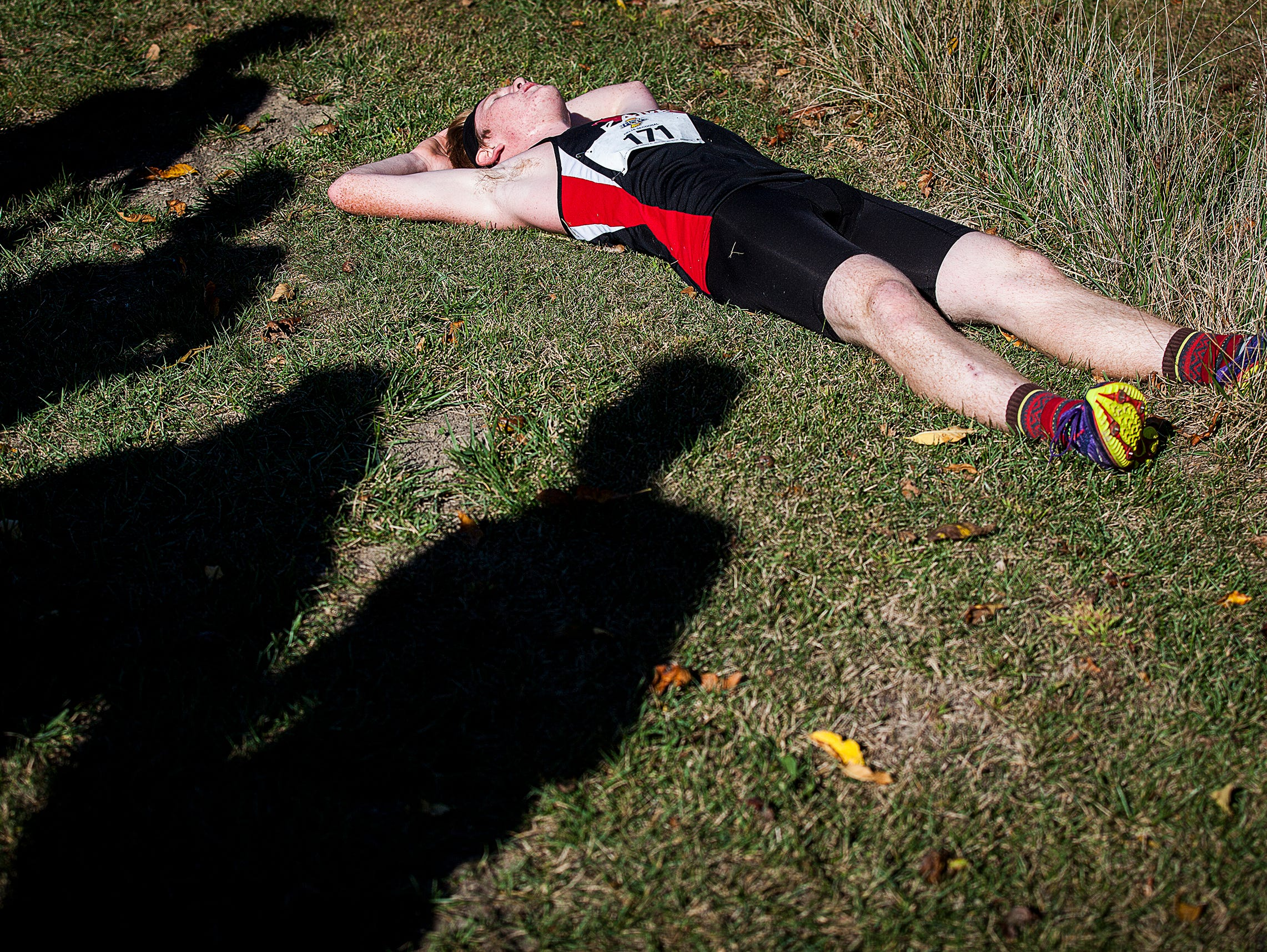 Wapahani's Daxton Stevens rests after finishing his his race during the cross country sectionals at the Sportsplex in Muncie on Saturday, Oct. 10, 2015.