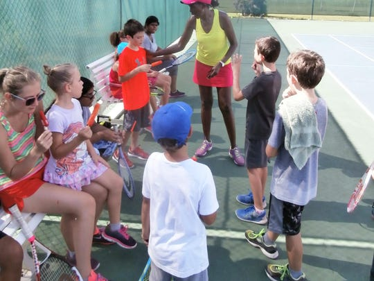It's time for water and a treat while director Sibo Kangwa talks tennis with kids at one of her morning camp sessions at Three Oaks Tennis Center at Barbara Manzo Park.