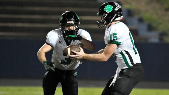 Mountain Heritage's  Trey Robinson (15) hands off the ball to Junior Denton, during Friday's win at West Henderson.