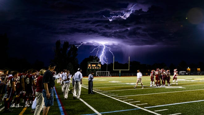 Lightning strikes beyond French Field as Rocky Mountain's football team huddles during a timeout in their game against Fossil Ridge Friday, September 19, 2014, at French Field in Fort Collins, CO.