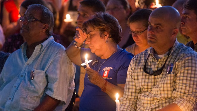 Patricia Gerald, mother of Matthew Gerald-  one of three Baton Rouge police officers killed in a July 17 shootout, wipes her eyes during a candlelight vigil for Gerald in Baton Rouge July 18.
