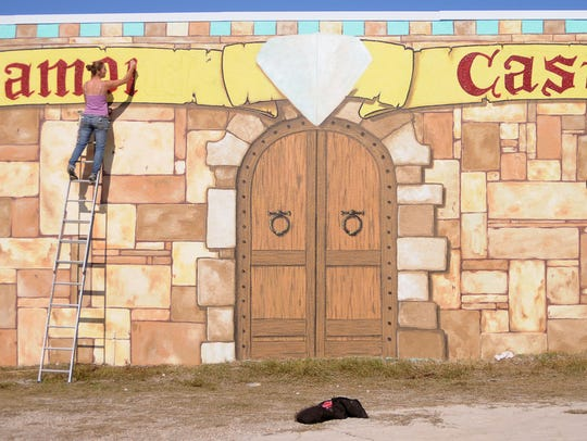 12/20/10----Jenna Zimmerman (left) and Nancy Lydon (right) with their business called Surfaces, finish painting the wall of the Diamond Castle Pawn Shop in Cocoa Beach. It took them about 7 days to finish the wall. Photo by: Michael R. Brown