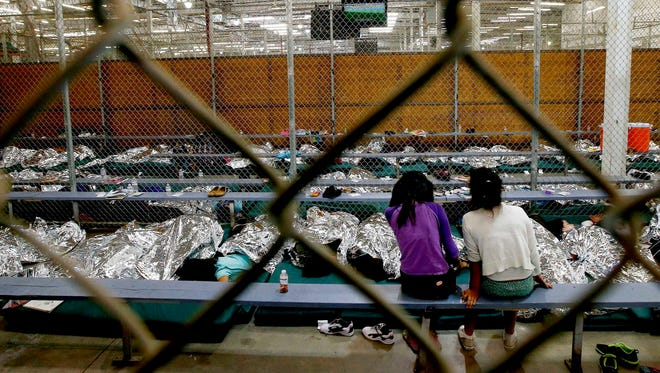 In this June 18, 2014, file photo, two young girls watch a World Cup soccer match on a television from their holding area where hundreds of mostly Central American immigrant children are being processed and held at the U.S. Customs and Border Protection Nogales Placement Center in Nogales, Ariz.