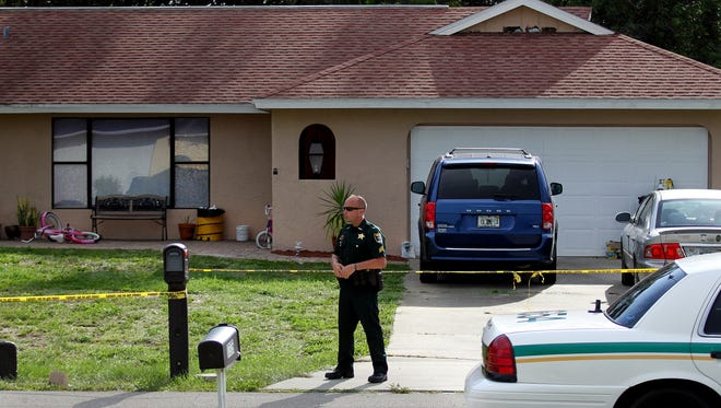 A Lee County Sheriff's Office deputy stands guard at the scene of a murder-suicide June 8, 2014 a Fort Myers, Fla., neighborhood.