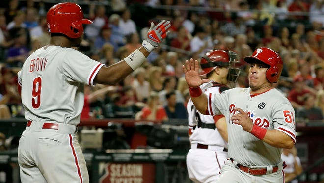 Philadelphia Phillies' Carlos Ruiz (51) gets a high-five from teammate Domonic Brown (9) after Ruiz scored a run against the Arizona Diamondbacks during the seventh inning of a baseball game on Friday, April 25, 2014, in Phoenix. (AP Photo/Ross D. Franklin)