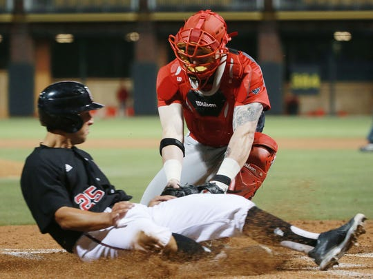 New Mexico catcher Chris DeVito tags out New Mexico State baserunner Mason Fishback Tuesday at Southwest University Park.