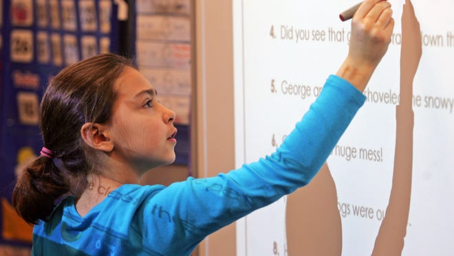 In this Jan. 10, 2014 photo third-grader Erin Uecker works on her classroom's Smart Board during a grammar lesson at Freeman Elementary in Freeman, S.D. A curriculum known as Common Core is being used in South Dakota classrooms and has drawn criticism from some educators. (AP photo/Jeremy Waltner)