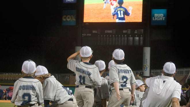 Youth baseball players watch themsevles on current scoreboard at Blue Wahoos Stadium during the recent Bill Bond League opening night celebration for its 50th anniversary. A new scoreboard will be installed for the upcoming Blue Wahoos season.
