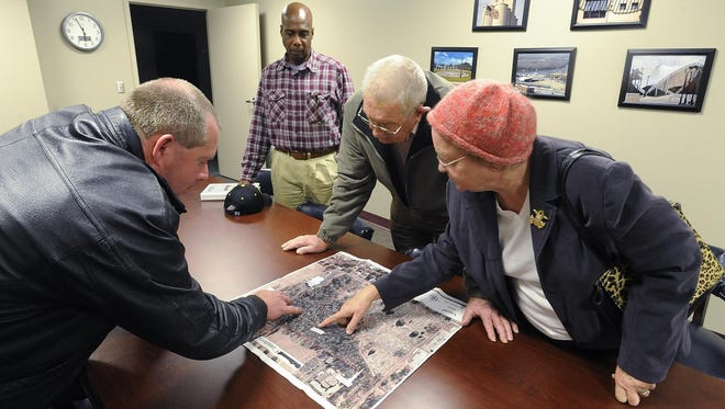 Phillip Taunton, left, Donald Jenkins, Darry Johnston and Janie Johnston look at a map following a meeting in December 2011 of the Lincoln Cemetery Rehabilitation Authority in Montgomery.