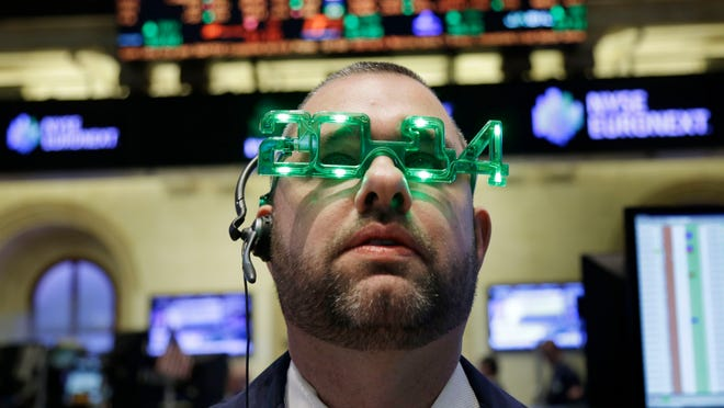 A trader wears glasses celebrating the new year while working on the floor at the New York Stock Exchange in New York, Tuesday, Dec. 31, 2013.