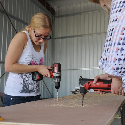 Britney Keanne Branch, left, and Janny Roy drill holes