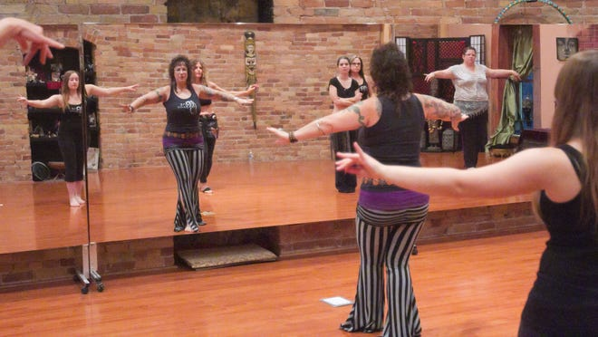 One Spirit Dance and Fitness owner Kelly Hassan (in striped pants) leads a class in belly dancing at her downtown Pinckney studio. Students shown in the mirror's reflection are, from left, Lindsay Lavish, Marlene Butkiewicz, Katrina Nussle, Amy Goble and Lesli Anderson.