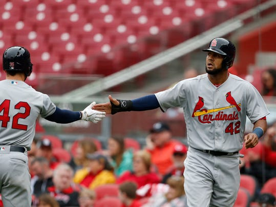 St. Louis Cardinals' Jose Martinez, right, slaps hands with Greg Garcia after scoring on a hit by Yadier Molina during the seventh inning of a baseball game against the Cincinnati Reds, Sunday, April 15, 2018, in Cincinnati. (AP Photo/Gary Landers)