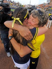 Carol Hutchins hugs pitcher Haylie Wagner after the Wolverines won the Super Regional on Friday night.