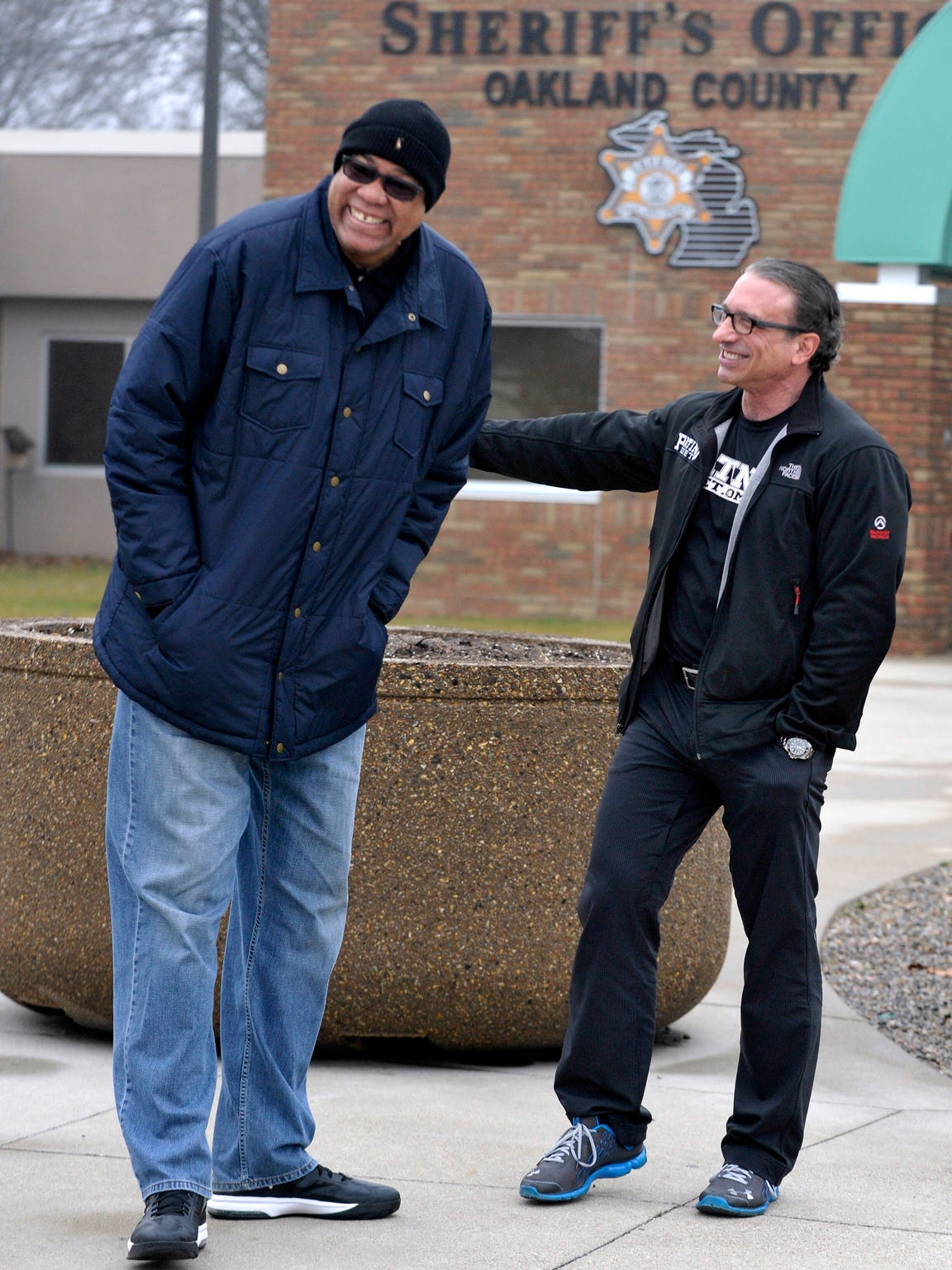 "Former Detroit Pistons player James Edwards, left, shares a laugh with Dr. Frank Patino as Oakland County Sheriff's deputies prepare to distribute 300 hams for holiday dinners during ""Operation Pig Out"" on Tuesday, Dec. 23, 2014."