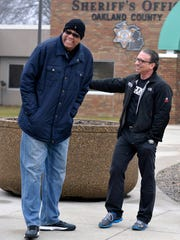 """Former Detroit Pistons player James Edwards, left, shares a laugh with Dr. Frank Patino while distributing 300 hams for holiday dinners during """"Operation Pig Out"""" in 2014."""