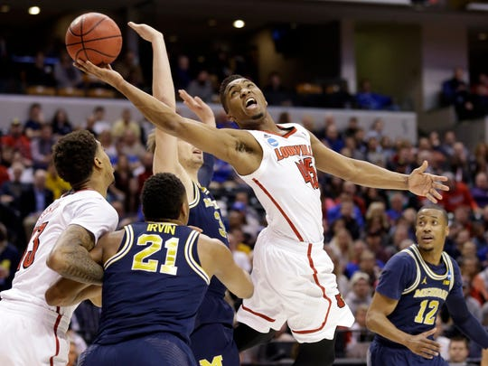 Louisville guard Donovan Mitchell (45) lays in a shot over Michigan guard Zak Irvin (21) during the first half of a second-round game in the men's NCAA college basketball tournament in Indianapolis, Sunday, March 19, 2017.
