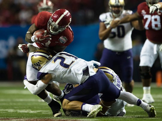 Washington defensive back Taylor Rapp tackles Alabama running back Bo Scarbrough (9) during the Peach Bowl playoff game between Alabama and Washington on Saturday, Dec. 31, 2016, at the Georgia Dome in Atlanta, Ga.