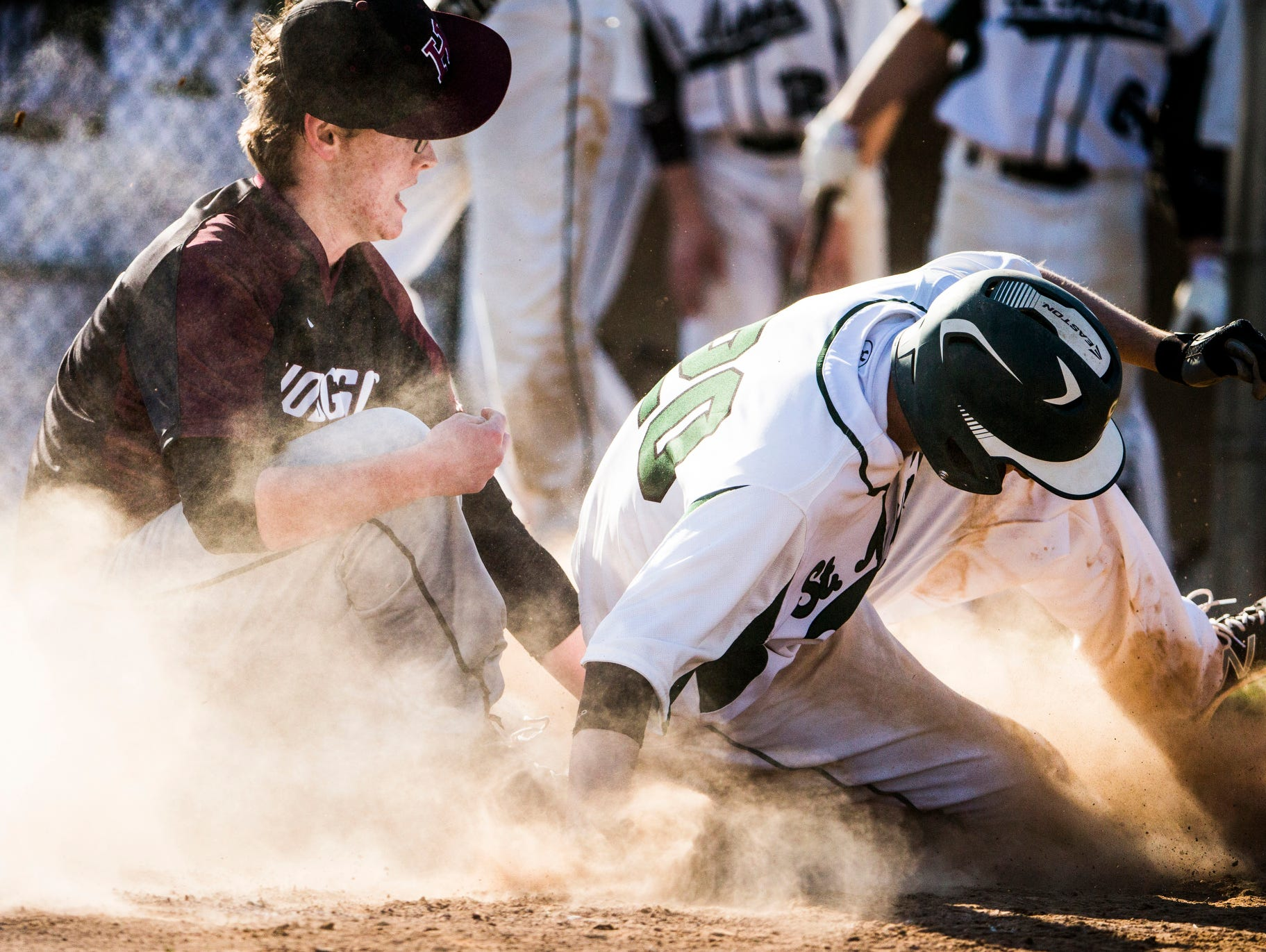 St. Mark's Christopher Ludman slides safely into home as Hodgson pitcher Daniel Brown tries to tag him out in a cloud of dust in St. Mark's 12-0 win over Hodgson at St. Mark's High School on Wednesday afternoon.