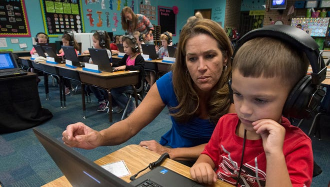 In this October photo, teacher Laurie Ann Bentley, left, assists student, Justin Pinckard, with connecting to a Wi-Fi network at S.S. Dixon Primary School in Pace. Santa Rosa County School District students use Dell touchscreen laptops. There are no immediate plans to invest in tablets.