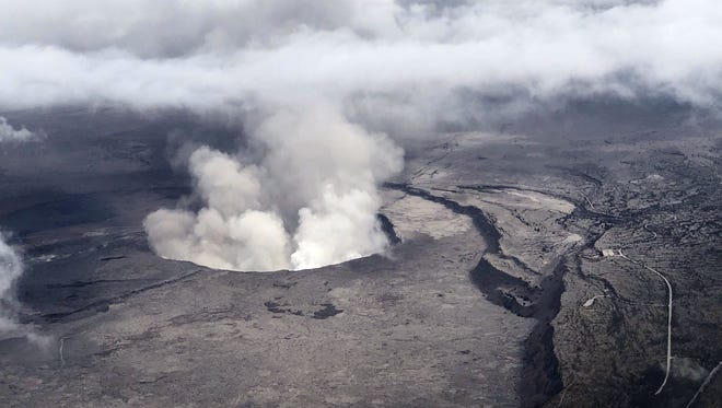 This image released by the US Geological Survey (USGS) courtesy of the Hawaii Civil Air Patrol, shows an aerial view of Kilauea Volcano's summit caldera and an ash plume billowing from Halemaumau, a crater within the caldera, on May 27, 2018. 