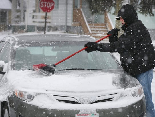 Jerry Hirt of Sheboygan brushes snow off his car.