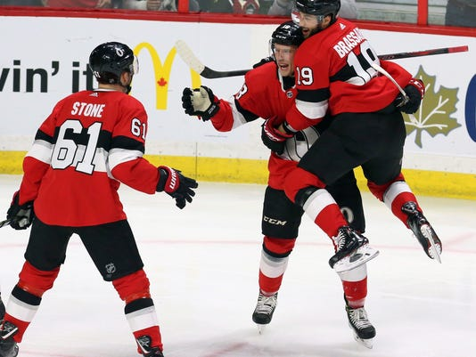 Ottawa Senators left wing Ryan Dzingel (18) celebrates his goal against the Tampa Bay Lightning with teammates Derick Brassard (19) and Mark Stone (61) during the first period of an NHL hockey game Saturday, Jan. 6, 2018, in Ottawa, Ontario. (Fred Chartrand/The Canadian Press via AP)