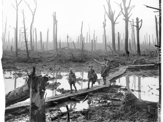 In this 1917 photo, Australian soldiers walk a duckboard track over mud and water in a denuded landscape near Ypres, the scene of intense fighting in the Great War.