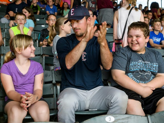 """Evansville Otters player Mitchell Aker (center) starts clapping to the """"Chicken Dance"""" song as he talks to West Elementary School fourth-graders Makayla Wallis (left) and Mason Chapman (right) during an Education Day Exhibition game against the Florence Freedoms at Bosse Field in Evansville, Ind., Wednesday, May 2, 2018. Several Otters players sat in the stands to greet and sign autographs for students during the game."""